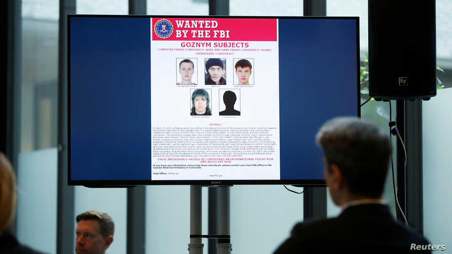 Suspects of cybercrime are seen on the screen at the news conference to announce a major law enforcement action against a transnational organized cybercrime at the Europol's headquarters in The Hague, Netherlands, May 16, 2019.