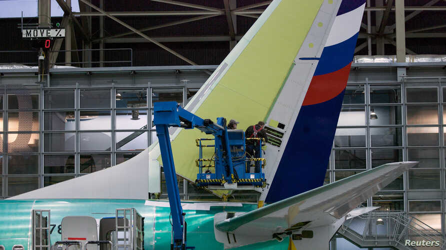 FILE PHOTO: Boeing employees work on the tail of a Boeing 737 NG at the Boeing plant in Renton, Washington December 7, 2015…