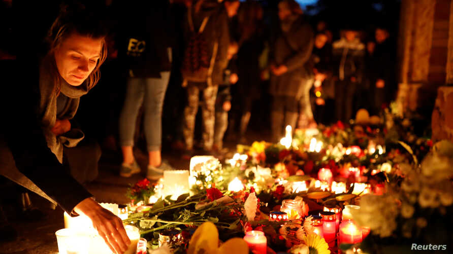 A woman places a candle at the synagogue in Halle, Germany October 10, 2019, after two people were killed in a shooting…