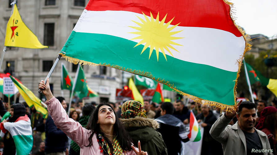 A woman flashes a V-sign as she waves a Kurdish flag during a pro-Kurdish rally against Turkey's military action in…