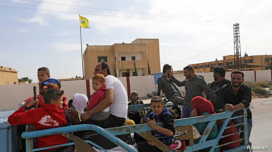 People ride on the back of a truck at the border town of Tal Abyad, Syria, October 14, 2019.