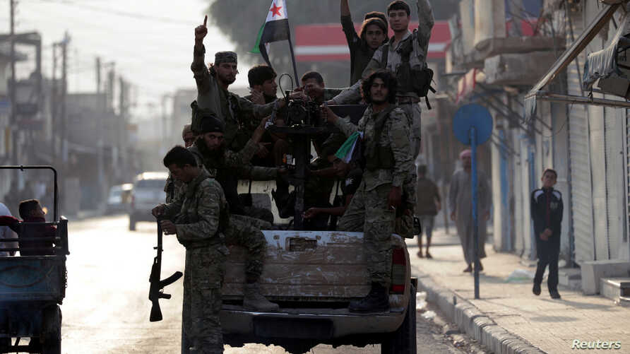 Turkey-backed Syrian rebel fighters gesture as they stand at a back of a truck in the border town of Tal Abyad, Syria, October…