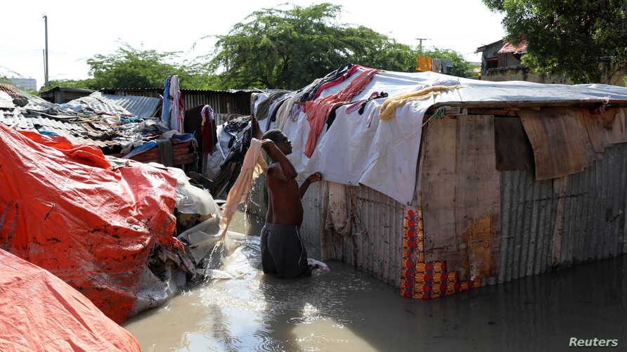 A Somali man airs his clothes dampened by flood waters on his makeshift shelter after heavy rain in Mogadishu, Somalia October…