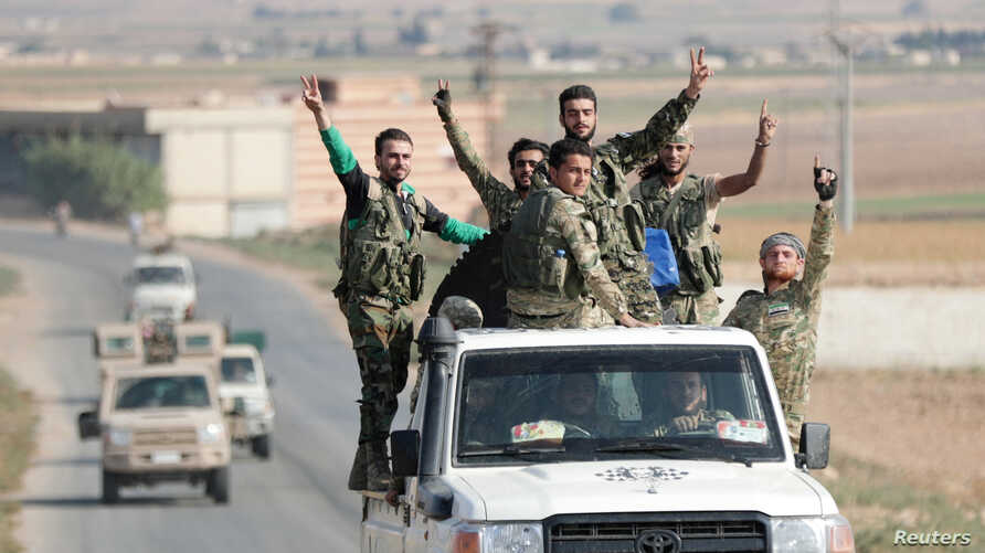 Turkey-backed Syrian rebel fighters gesture as they ride on a vehicle near the border town of Tal Abyad, Syria, October 22,…