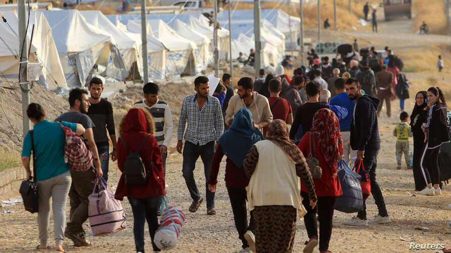 Syrian displaced families, who fled violence after the Turkish offensive in Syria, are seen upon arrival at a refugee camp in…