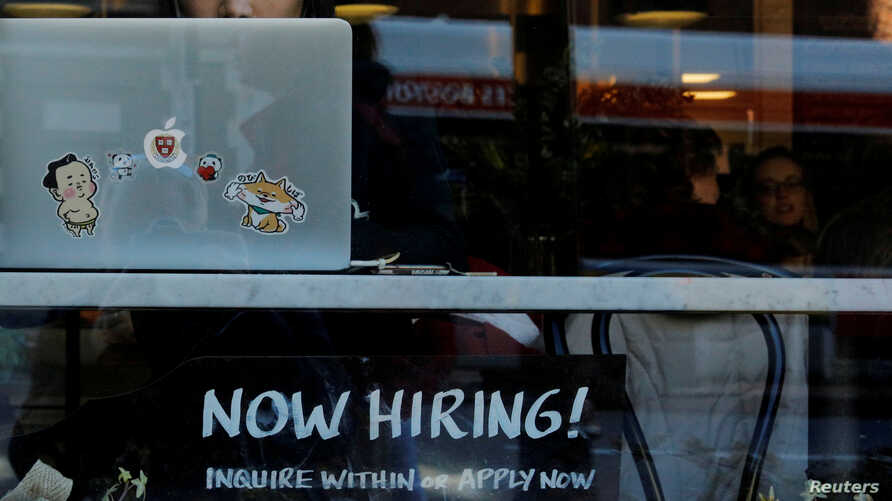 """FILE PHOTO: A """"Now Hiring"""" sign sits in the window of Tatte Bakery and Cafe in Cambridge, Massachusetts, U.S., February 11,…"""
