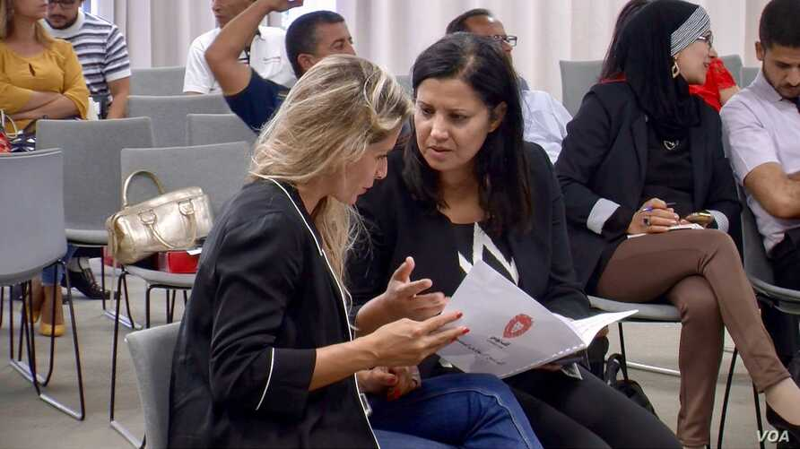 Samira Chaouachi (R) with colleagues at a recent Heart of Tunisia party meeting in Tunis. (L. Bryant/VOA)