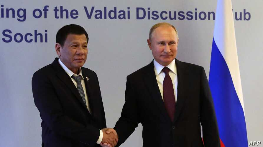 Russian President Vladimir Putin (R) shakes hands with Philippine's President Rodrigo Duterte prior to their meeting at the Valdai Discussion Club in Sochi, Russia, Oct. 3, 2019.