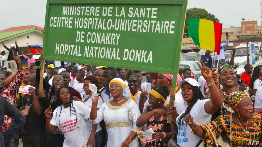 "Demonstrators hold a sign reading ""Health ministery, Conakry's University Hospital (CHU), Donka's national hospital"" as supporters of Guinea's President Alpha Conde take part in a rally in support of the President in Conakry on October 31, 2019."