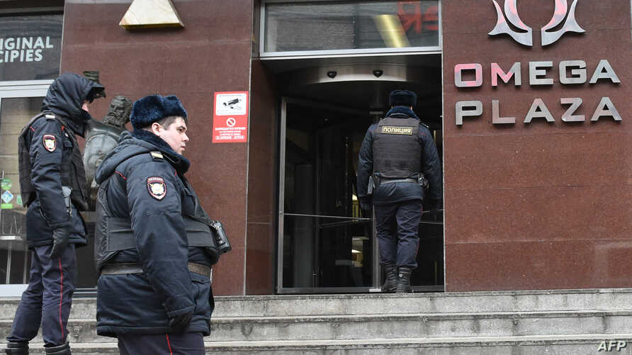FILE - Russian police officers gather at the entrance to a business center housing the office of opposition leader Alexei Navalny's Anti-Corruption Foundation (FBK), in Moscow, Russia, Jan. 28, 2018.