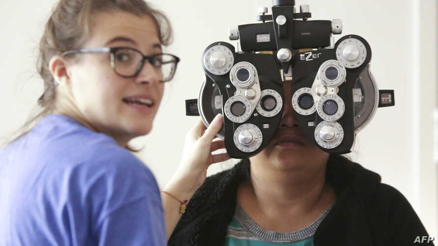 FILE - A woman gets an eye exam during a clinic at Key Arena, in Seattle, Washington, Oct. 28, 2016.