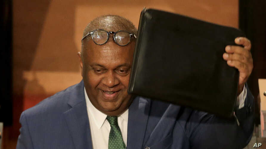 FILE - Sri Lanka's finance minister Mangala Samaraweera, center, shows his folder carrying government's budget proposal for the year 2019 to opposition as he enters the Parliament in Colombo, Sri Lanka, March 5, 2019.