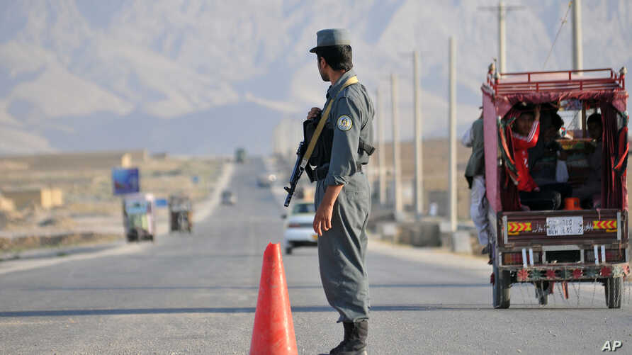 FILE - An Afghan policeman stands guard at a checkpoint on the outskirts of Mazar-i-Sharif, in Balkh province, Sept. 5, 2015
