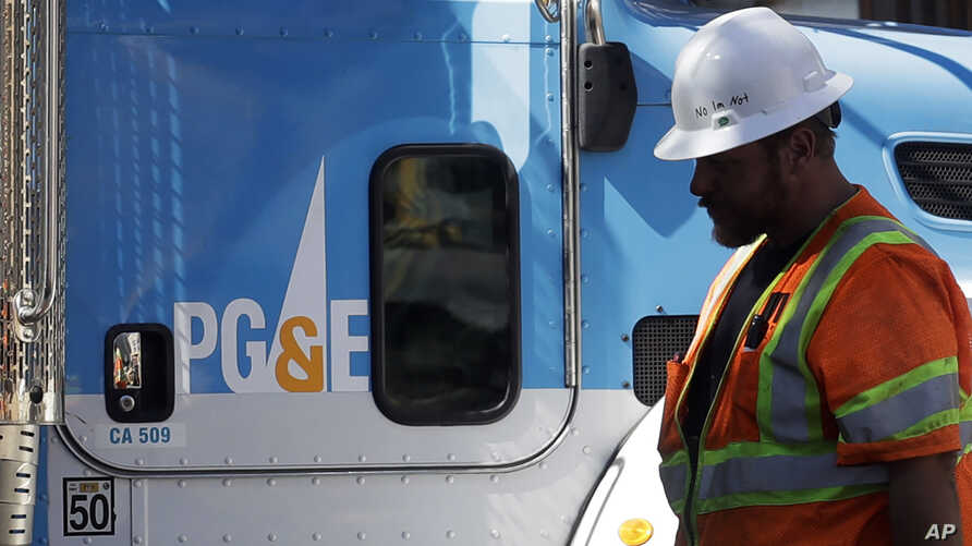 FILE - A Pacific Gas & Electric worker walks in front of a truck in San Francisco, California, Aug. 15, 2019.