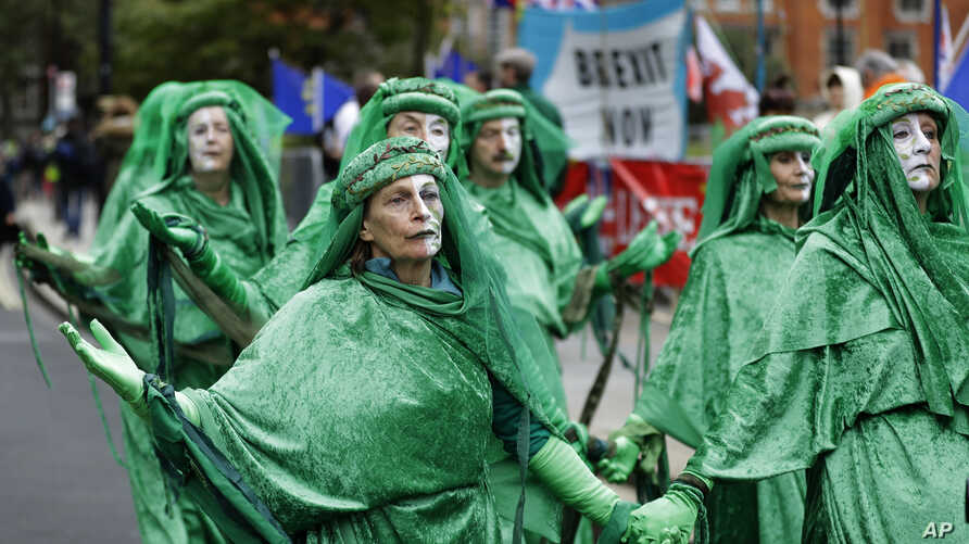 Climate protesters pass Brexit banners and flags outside Parliament in London, Britain, Oct. 8, 2019.