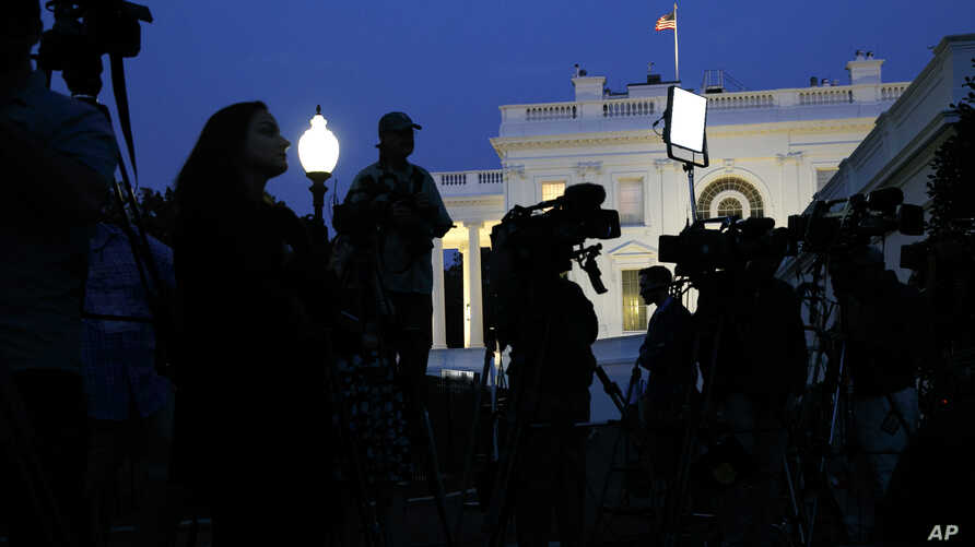 Dusk falls over the White House as members of the media wait for comment from Charlotte Charles and Tim Dunn, the parents of Harry Dunn, at the White House in Washington, Oct. 15, 2019.