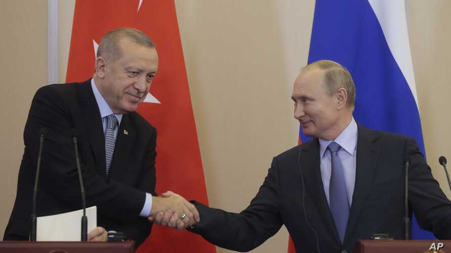 Russian President Vladimir Putin, right, and Turkish President Recep Tayyip Erdogan shake hands after their joint news conference following their talks in the Bocharov Ruchei residence in the Black Sea resort of Sochi, Russia, Oct. 22, 2019.
