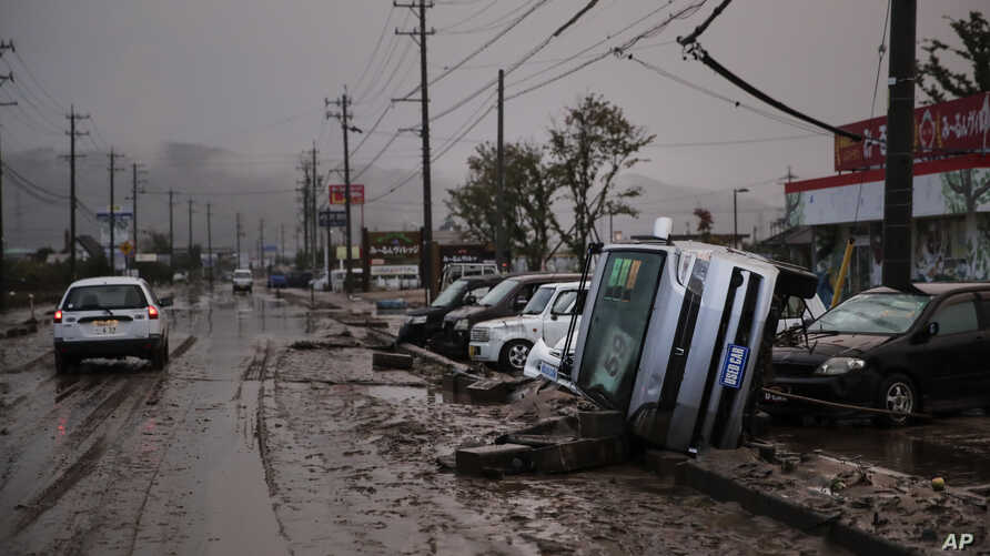 Typhoon-damaged cars sit on the street covered with mud, Oct. 14, 2019, in Hoyasu, Japan.