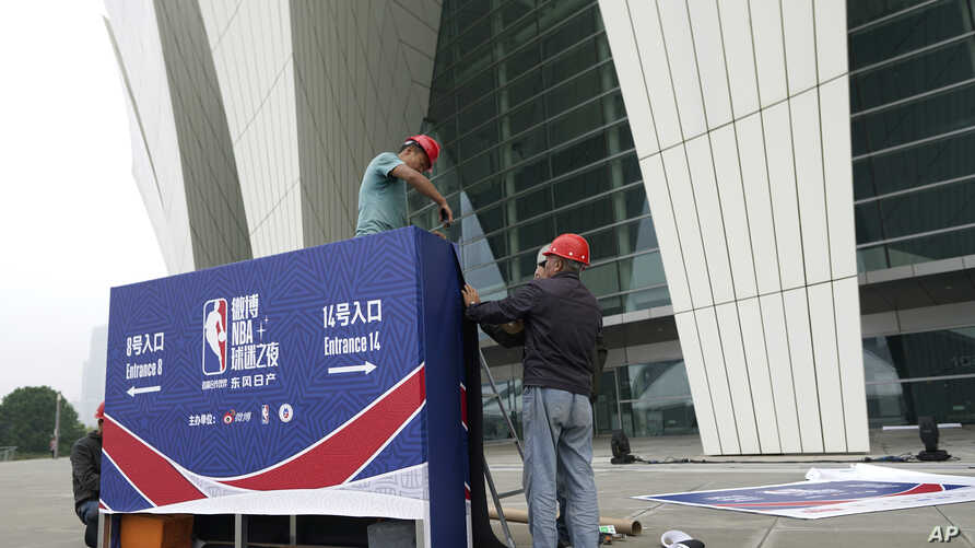 Workers dismantle signage for an NBA fan event that was scheduled to be held at the Shanghai Oriental Sports Center in Shanghai, China, Oct. 8, 2019.