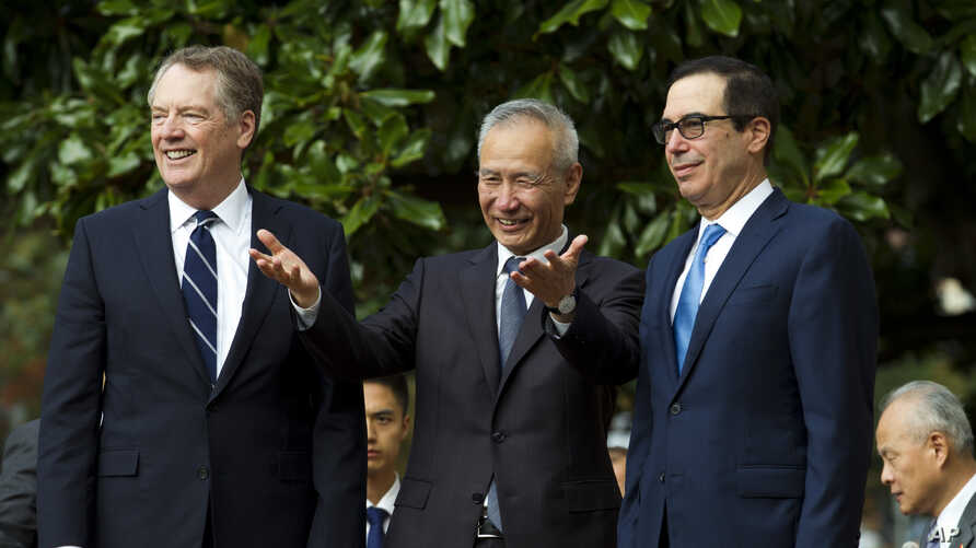 Chinese Vice Premier Liu He, center, flanked by U.S. Trade Representative Robert Lighthizer, left, and Treasury Secretary Steven Mnuchin, gestures to the media before a ministerial-level trade meeting in Washington, Oct. 10, 2019.