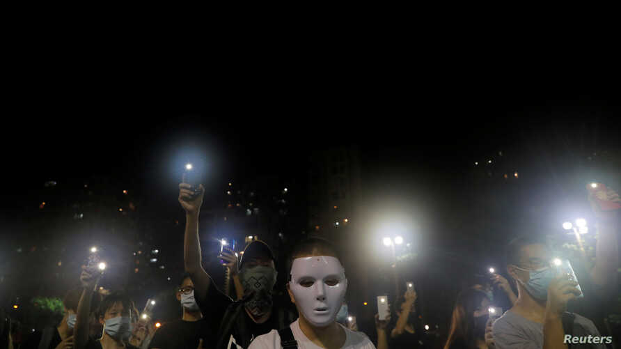 Masked pro-democracy protesters hold up their phones during a rally in Tsim Sha Tsui district, Hong Kong, Oct. 5, 2019.