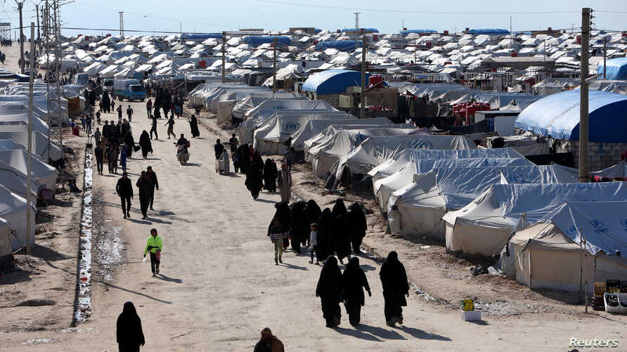 FILE - Women, who lived in the Islamic State's so-called caliphate, walk through al-Hol camp in Hasaka province, Syria, April 1, 2019.