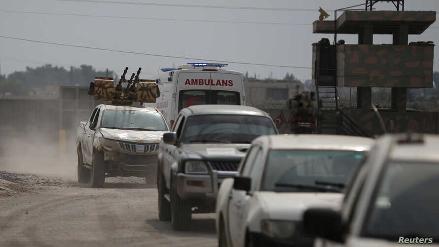 Turkey-backed Syrian rebel fighters return from the Syrian border town of Tal Abyad, on the Turkish-Syrian border in Akcakale, Turkey, Oct. 19, 2019.