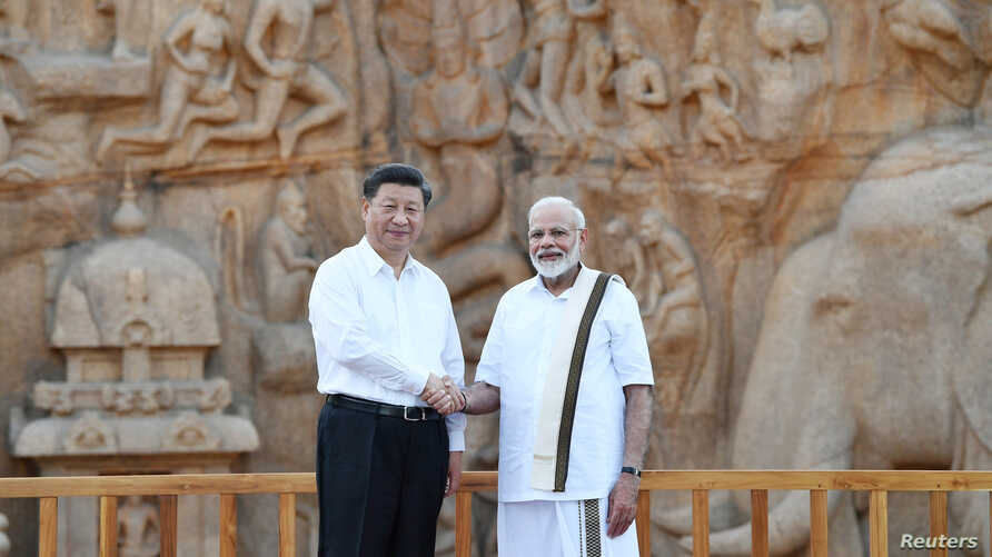 China's President Xi Jinping, left, shakes hands with India's Prime Minister Narendra Modi during their visit to Arjuna's Penance, in Mamallapuram on the outskirts of Chennai, India, Oct. 11, 2019.