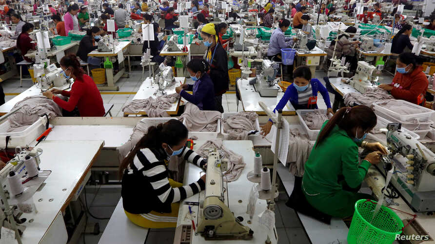 FILE - Employees work at a factory supplier of the H&M brand in Kandal province, Cambodia, Dec. 12, 2018.