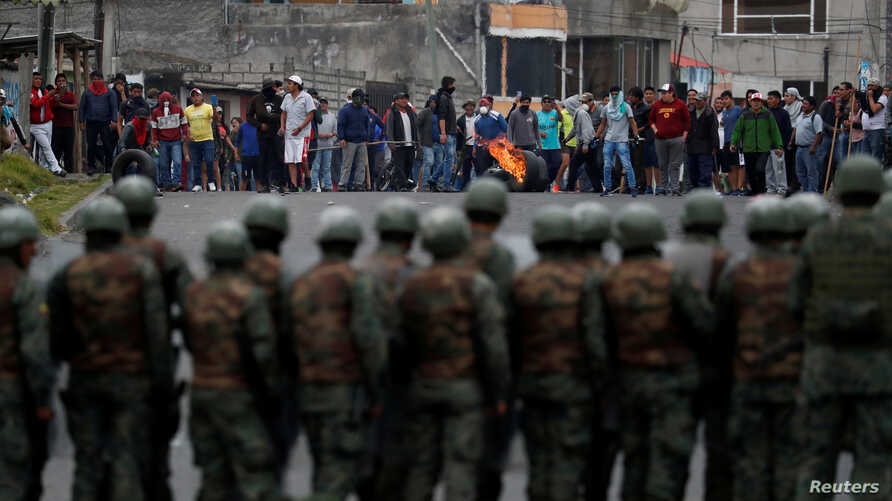Soldiers line up as people block a road during protests after Ecuador's President Lenin Moreno's government ended four-decade-old fuel subsidies, in Lasso, Ecuador, Oct. 6, 2019.