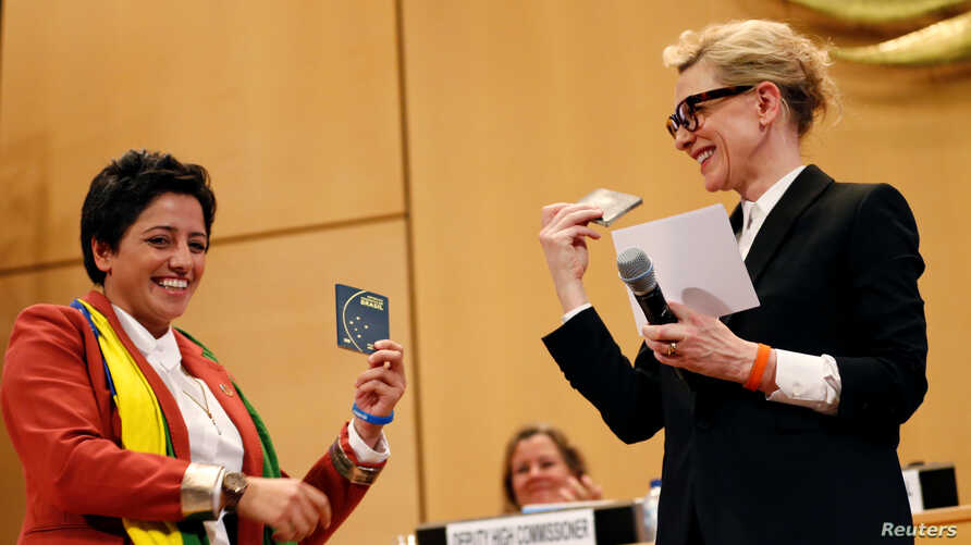 UNHCR goodwill ambassador and actress Cate Blanchett (R) and formerly stateless refugee Maha Mamo (L) show passports as they attend a High-Level Segment on Statelessness during the UNHCR's Executive Committee meeting in Geneva, Switzerland, Oct. 7, 2019.