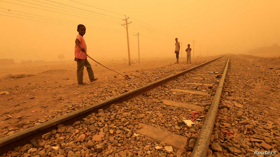FILE - Children play near railways during a sandstorm in Khartoum, Sudan, March 29, 2018.