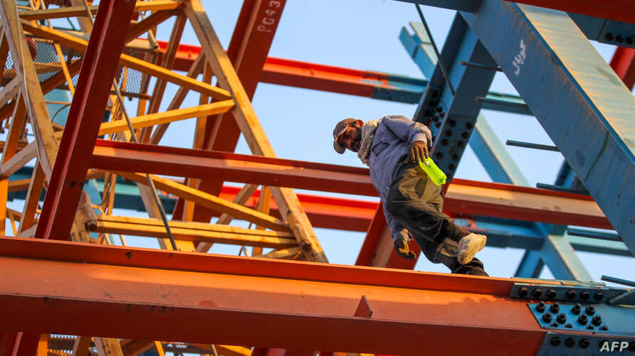 An Iranian construction worker walks on a steel I-beam at a site for a future bank tower in the Iraqi capital Baghdad's central…