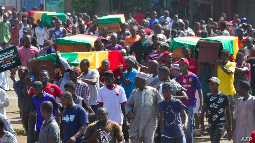 People carry coffins during the funeral after last street protests and unrest that resulted in nine deaths in Conakry, on…