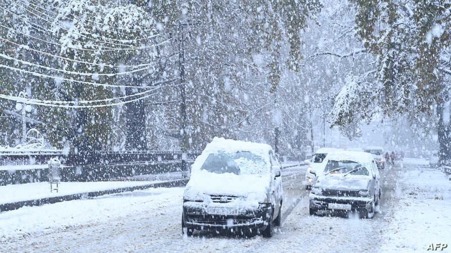 Cars covered in snow drive along a road during a first snowfall in Srinagar on November 7, 2019. (Photo by Tauseef MUSTAFA /…