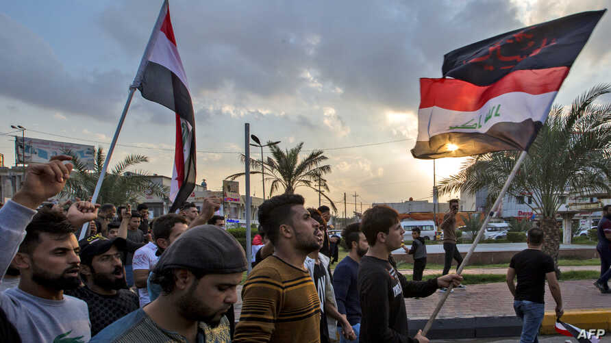 """Iraqi protesters march with national flags and a Shiite Muslim flag reading in Arabic """"oh martyr Hussein"""" during an anti…"""