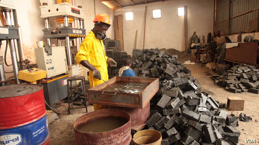 Inside Nelson Boateng's Nelplast factory in the outskirts of Accra, Ghana, a worker creates bricks from recycled plastic and sand, Nov. 12, 2019. (Stacey Knott/VOA)