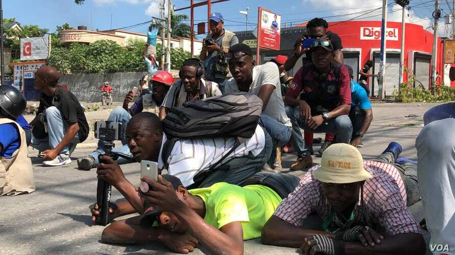 Haitian journalists lay on the street to avoid being shot during altercation between Haitian National Police and protesters, Oct. 31, 2019 in Port-au-Prince, Haiti. (Photo: Matiado Vilme)