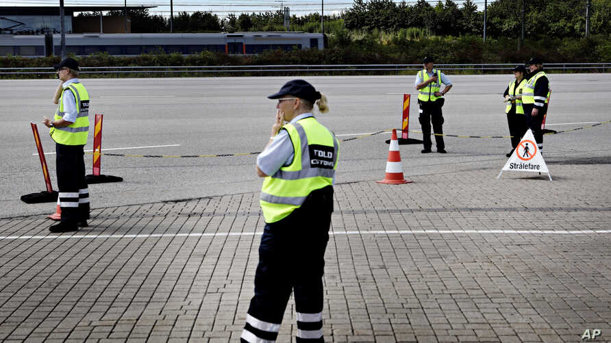 FILE - Danish customs officials stand ready at the Danish border to Sweden at on the Oeresund Bridge, Denmark, July 5, 2011.