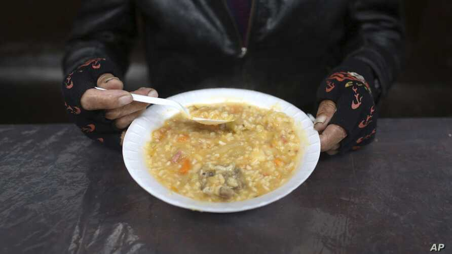 """A man eats his soup during """"La Porciuncula,"""" a religious event where Franciscans monks serve food to the poor, at the Los…"""