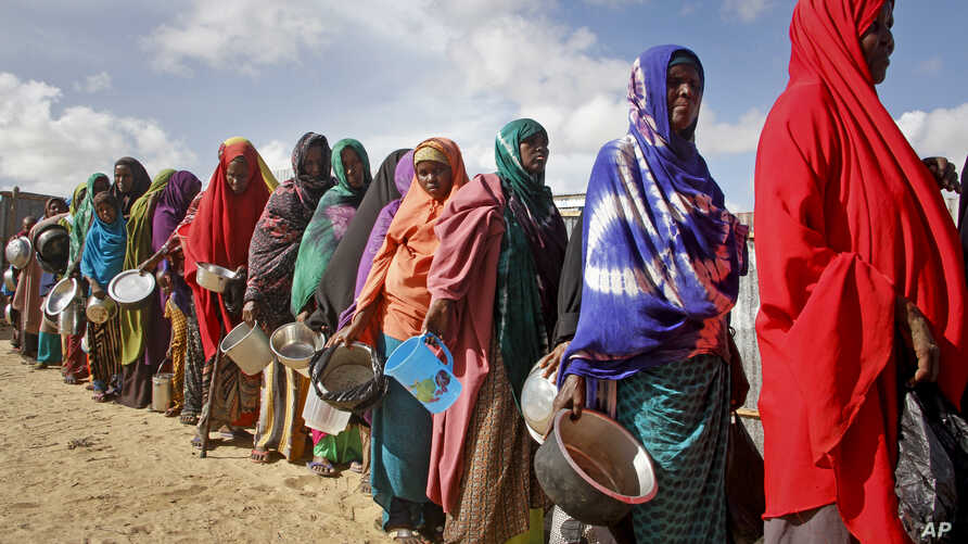 Newly-arrived women who fled drought queue to receive food distributed by local volunteers at a camp for displaced persons in…