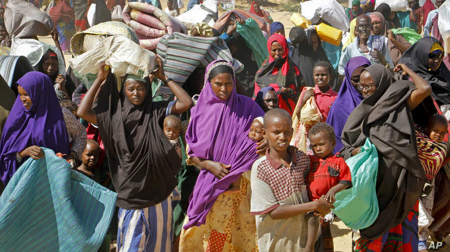 FILE - People fleeing from drought in the Lower and Middle Shabelle regions of Somalia carry their belongings as they reach a makeshift camp for displaced persons in the Daynile neighborhood on the outskirts of the capital Mogadishu, May 18, 2019.