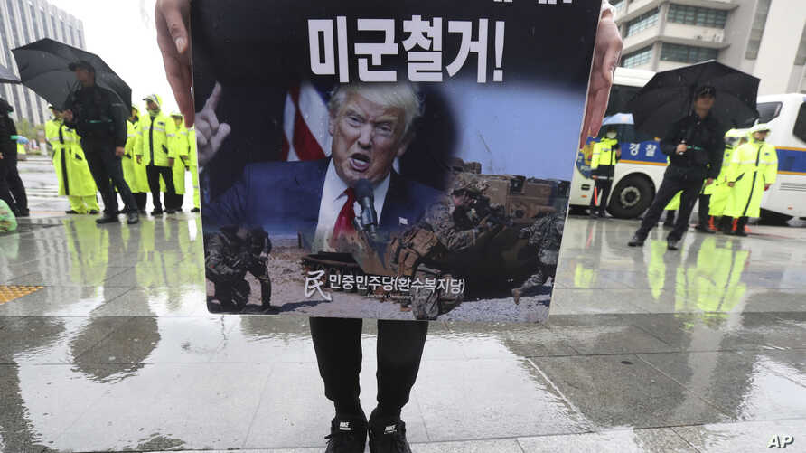 A protester holds a banner showing an image of U.S. President Donald Trump during a rally to oppose the United States' policies…