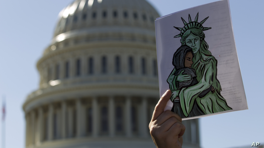 Faith leaders and members of human rights groups protest outside of the U.S. Capitol during a demonstration calling congress…