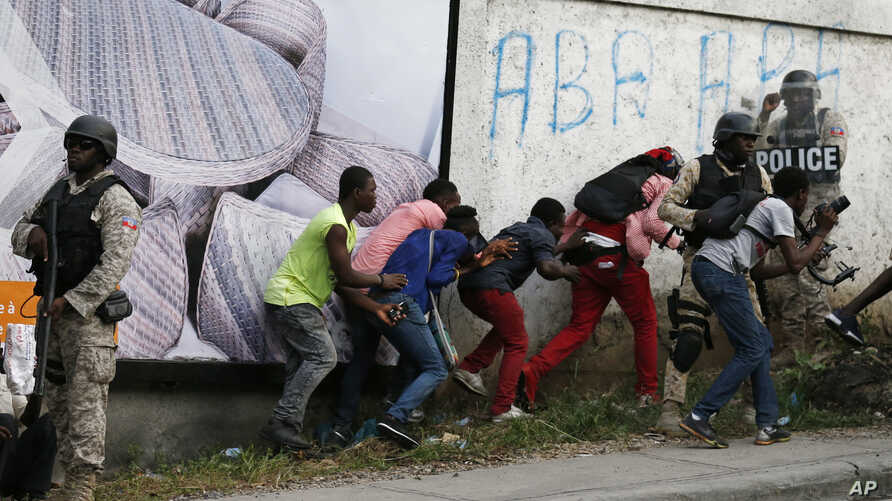 Members of the press take cover as clashes with police break out at the end of an anti-government march called by the artist…