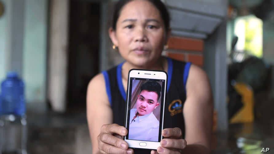 Hoang Thi Ai holds up her phone showing a photo of her son Hoang Van Tiep, who she fears is one of the possible victims in the…