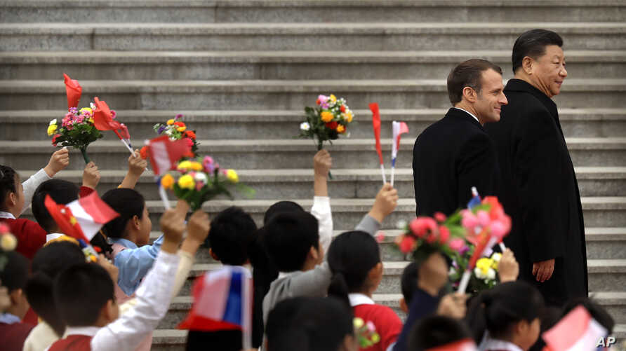 French President Emmanuel Macron, left, and Chinese President Xi Jinping react as schoolchildren wave Chinese and French flags…