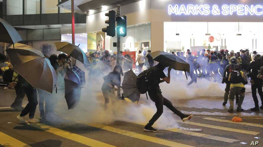 A protestor kicks away a police teargas shell as they clash outside a shopping mall in Hong Kong, Nov. 10, 2019.