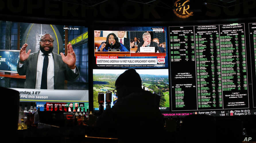 The first public impeachment hearing of President Donald Trump plays on a screen at the Superbook sports book inside the…