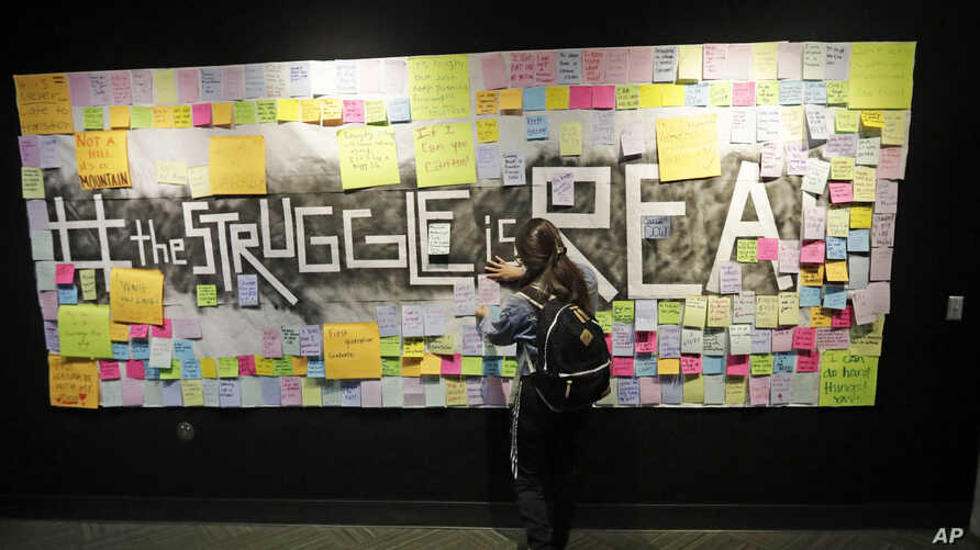 In this Nov. 14, 2019, photo, a student attaches a note to the Resilience Project board on the campus of Utah Valley University…